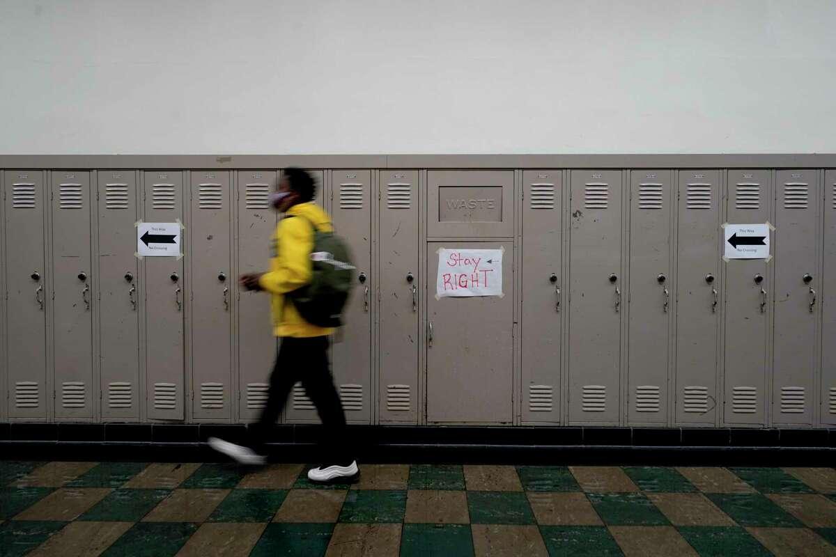Un alumno camina por el pasillo de una escuela en la secundaria del condado Wyandotte, en Kansas City, el 31 de marzo de 2021.