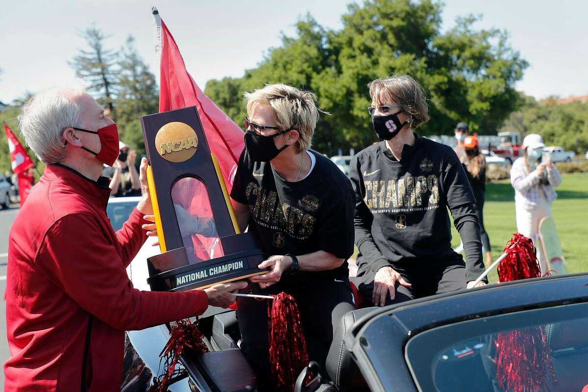 Stanford President Marc Tessier-Lavigne hands the NCAA trophy back to Kate Paye, assistant coach, at center, and Tara VanDerveer, head coach, as the Stanford women's basketball team celebrates their NCAA Basketball Championship win with a parade at Stanford University on Monday, April 5, 2021, in Stanford, Calif.
