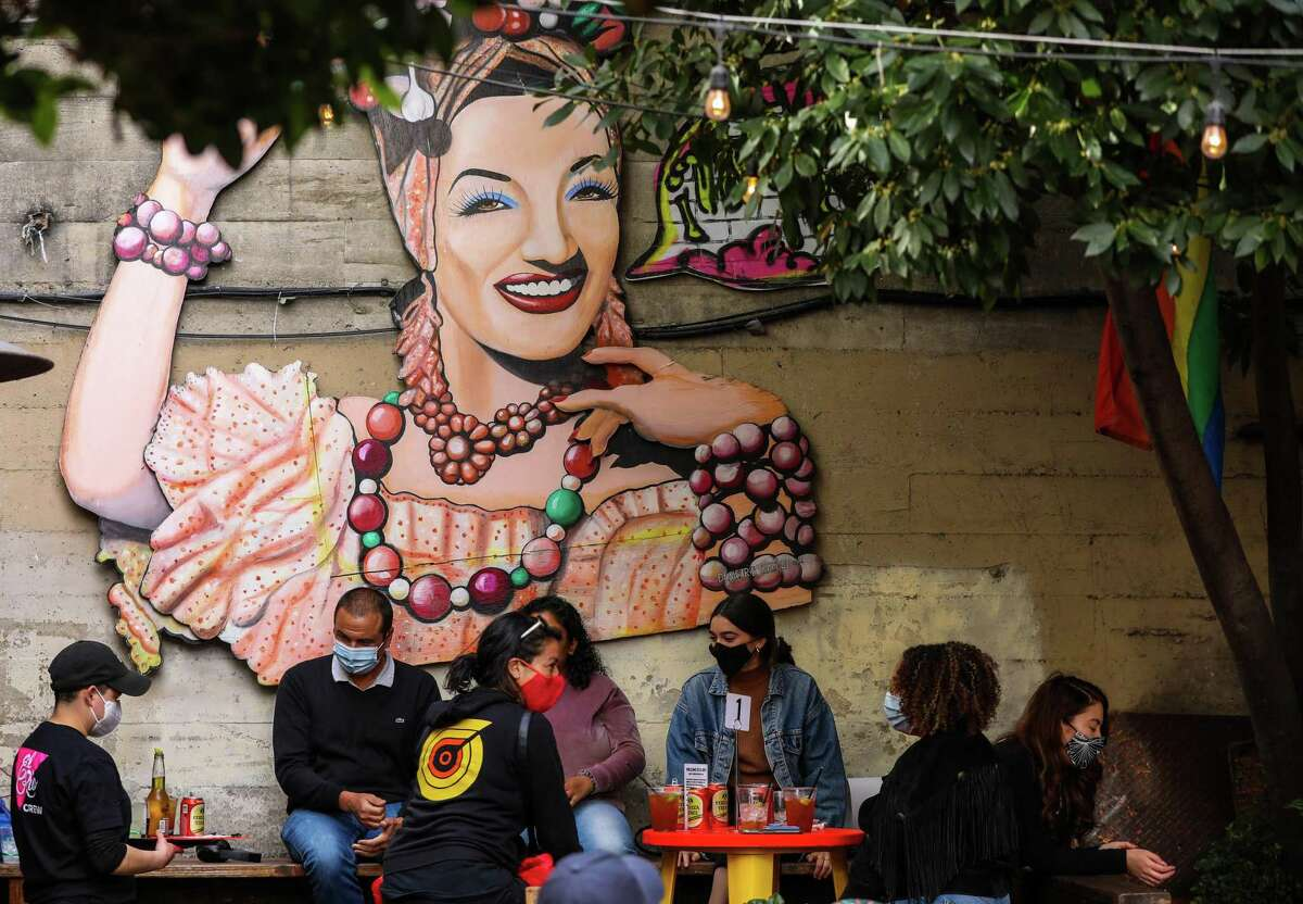 Patrons enjoy drinks on the patio of El Rio in front of a mural of samba singer Carmen Miranda.