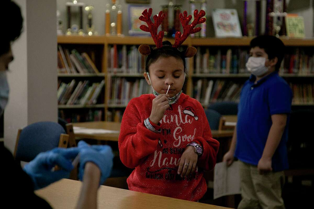 Stafford Elementary School student Brianna Avila Chavez swabs her nose for a COVID-19 test by Community Labs in the school's library on Dec. 9, 2020. Edgewood ISD, with Community Labs, began offering COVID-19 testing at all campuses that day. Bexar County commissioners have committed spending another $2 million for testing by Community Labs.