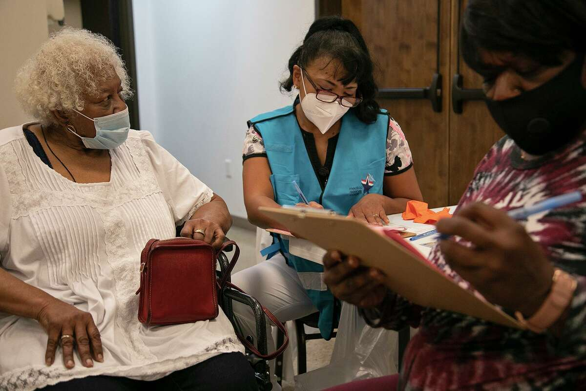 Dorothy Brewer, 86, and her niece, Geneva Pope, wait as nurse and volunteer Mary Young prepares them for their second dose of the COVID-19 vaccine at Bethel AME Church in San Antonio on April 5, 2021.