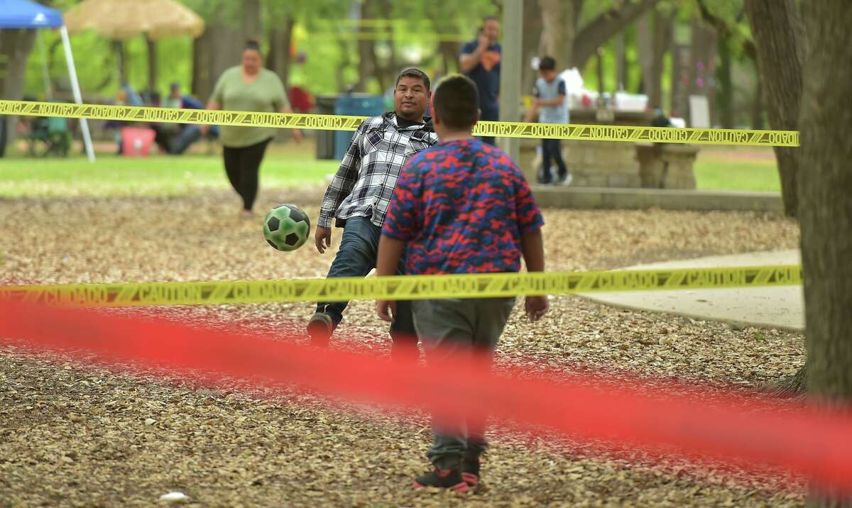 Efrain Saavedra plays soccer with his son Leonardo at a family gathering Easter Sunday in Brackenridge Park. Coronavirus restrictions that prohibited San Antonians from enjoying picnics in the park last Easter were lifted this year as the number of new cases continues to drop.