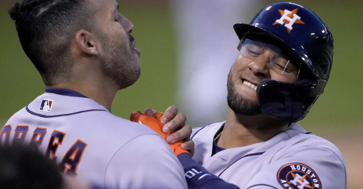 Houston Astros' Yuli Gurriel, right, is congratulated by Carlos Correa, left, after hitting a solo home run against the Oakland Athletics during the fourth inning of a baseball game Friday, April 2, 2021, in Oakland, Calif. (AP Photo/Tony Avelar)