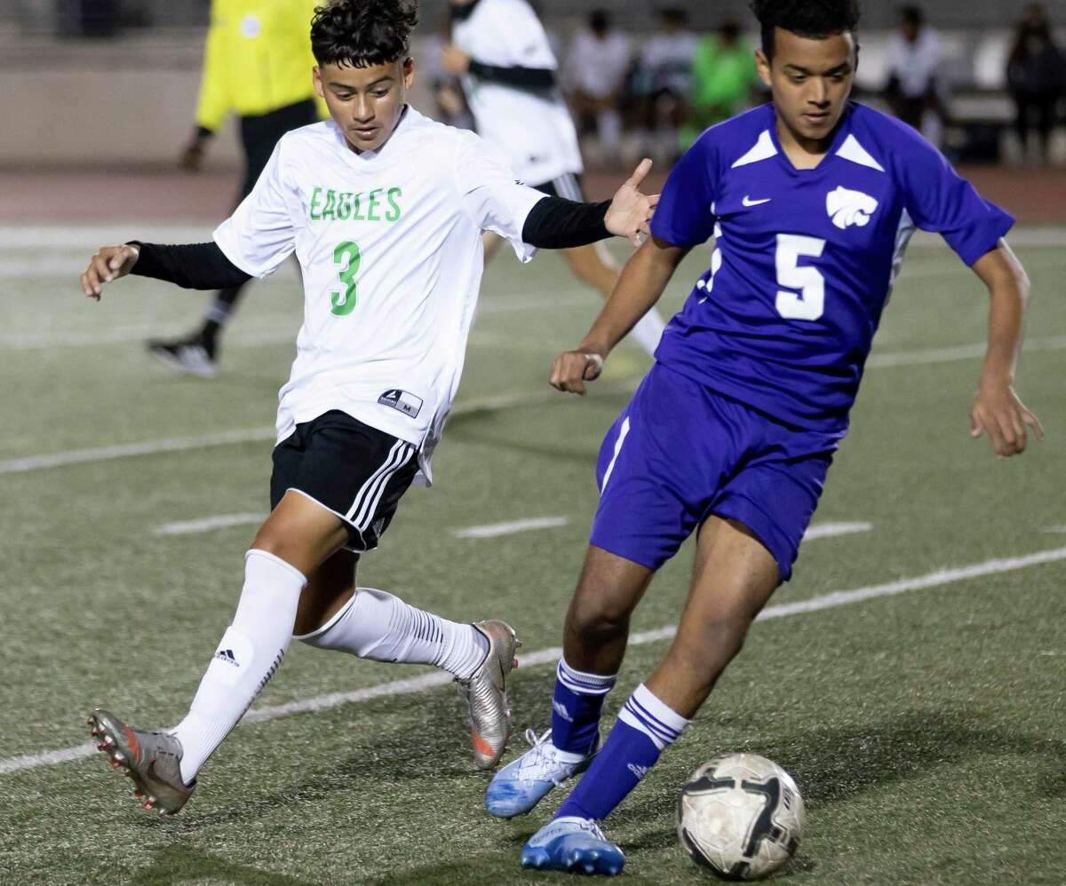 Humble midfielder Josue Zapata (5) drives the ball while under pressure from Pasadena Emanuel Delgado (3) during the first half of a non-district soccer match at George Turner Stadium, Tuesday, Jan. 19, 2021, in Humble.