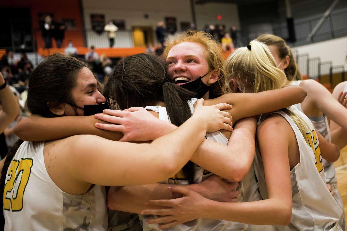 Dow's Alexa Kolnitys hugs her teammates after their state quarterfinal victory over Hartland Monday, April 5, 2021 at Flushing High School. (Katy Kildee/kkildee@mdn.net)