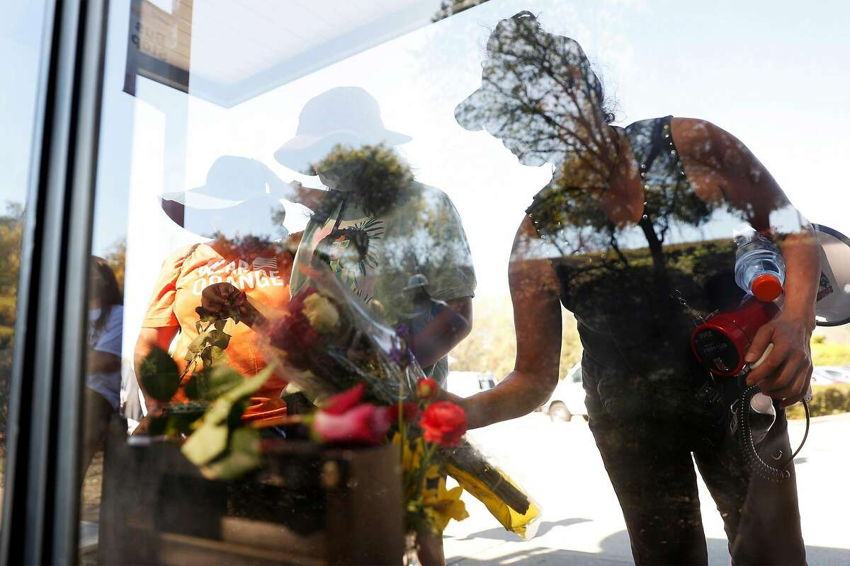 Before marching to Danville Police headquarters, people lay flowers at a Sycamore Park and Ride bus shelter near where homeless man, Tyrell Wilson, was shot and killed by the same Danville Police officer who shot and killed Laudemer Arboleda in November 2018. Photographed on Sunday, March 28, 2021, in Danville, Calif., for
