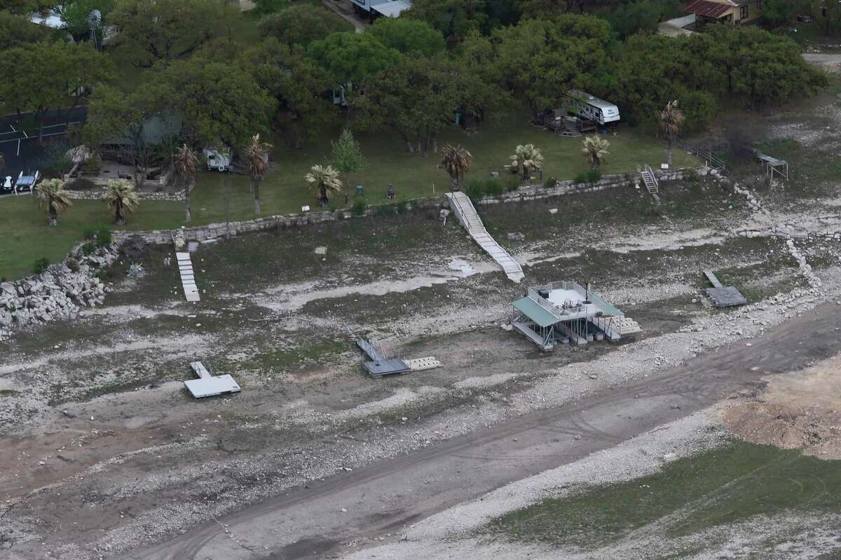 Docks are seen on land at Medina Lake, Monday, April 5, 2021.The lake is down to 37 percent capacity. The Edwards Aquifer Authority declared stage one pumping reductions last Wednesday after discovering the main well in Bexar County dropped below the 660-foot threshold to 659.7 feet above the mean sea level. This means people from Bexar, Atascosa, Caldwell, Comal, Guadalupe, Hays and Medina counties using the aquifer?•s groundwater need to reduce their water consumption by about 20 percent in order to stabilize water levels. As of noon Thursday, the well?•s level was even lower at 656.4 feet, according to Edwards Aquifer Authority data.