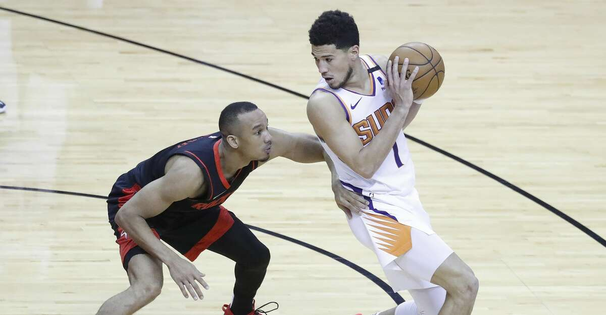 Phoenix Suns guard Devin Booker (1) works against Houston Rockets guard Avery Bradley (9) during the fourth quarter of an NBA basketball game at Toyota Center, Monday, April 5, 2021.