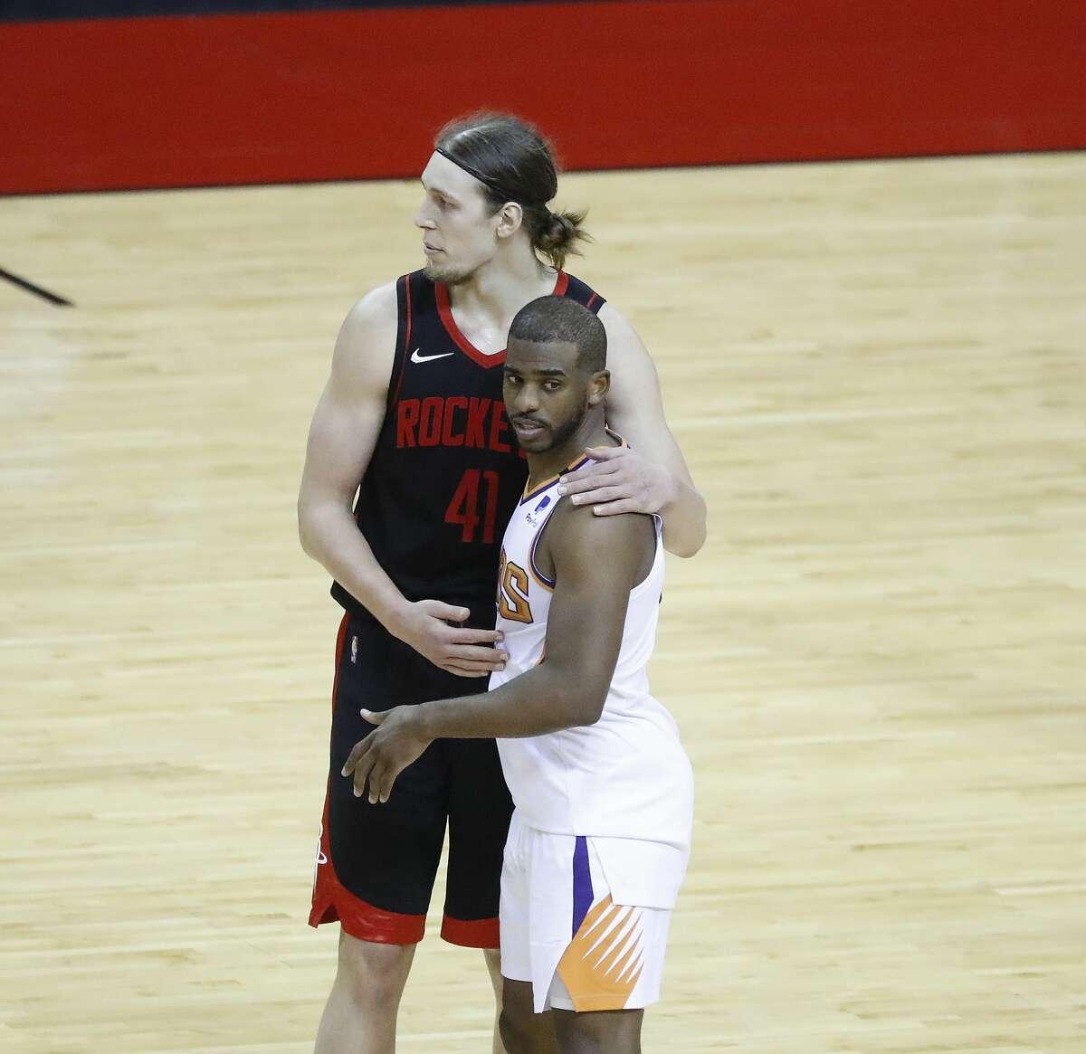 Houston Rockets forward Kelly Olynyk (41) hugs Phoenix Suns guard Chris Paul (3) after an NBA basketball game at Toyota Center, Monday, April 5, 2021.