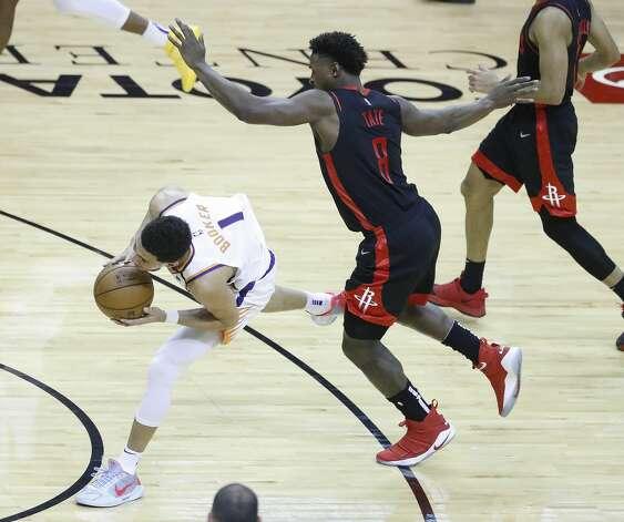 Houston Rockets forward Jae'Sean Tate (8) fouls Phoenix Suns guard Devin Booker (1) during the fourth quarter of an NBA basketball game at Toyota Center, Monday, April 5, 2021. Photo: Karen Warren/Staff Photographer / @2021 Houston Chronicle