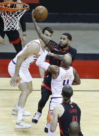 Houston Rockets guard D.J. Augustin (14) goes up for a basket against Phoenix Suns guard Jevon Carter (4) during the second quarter of an NBA basketball game at Toyota Center, Monday, April 5, 2021. Photo: Karen Warren/Staff Photographer / @2021 Houston Chronicle