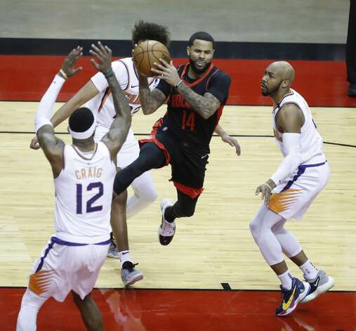 Houston Rockets guard D.J. Augustin (14) looks to pass the ball against Phoenix Suns forward Torrey Craig (12) and guard Jevon Carter (4) during the first half of an NBA basketball game at Toyota Center, Monday, April 5, 2021. Photo: Karen Warren/Staff Photographer / @2021 Houston Chronicle