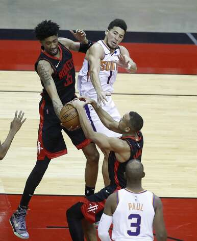 Houston Rockets center Christian Wood (35) and guard Avery Bradley (9) fight for a rebound with Phoenix Suns guard Devin Booker (1) during the first half of an NBA basketball game at Toyota Center, Monday, April 5, 2021. Photo: Karen Warren/Staff Photographer / @2021 Houston Chronicle