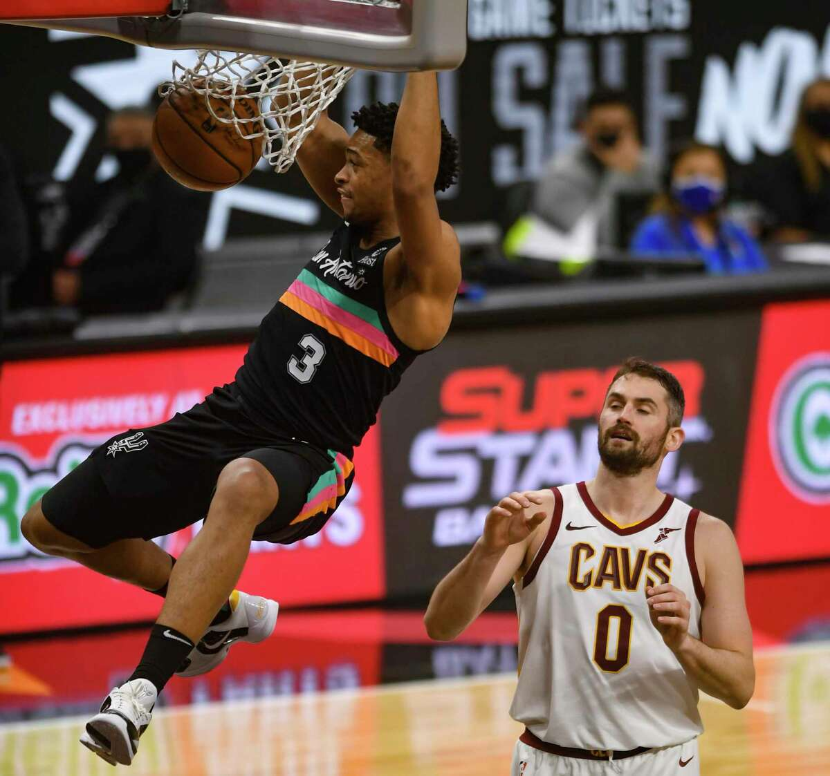 Keldon Johnson of the San Antonio Spurs dunks as Kevin Love of the Cleveland Cavaliers stands by during NBA action in the AT&T Center on Monday, April 5, 2021.