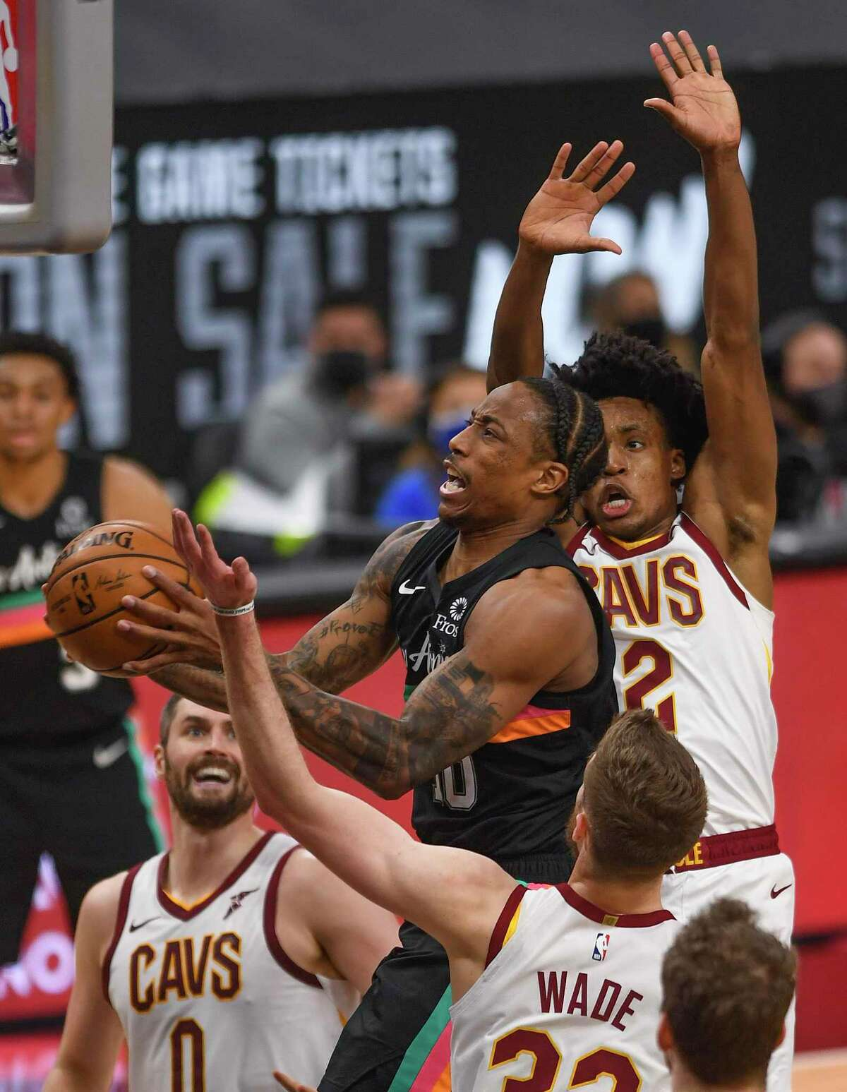 DeMar DeRozan of the San Antonio Spurs drives and shoots as Kevin Love (0), Collin Sexton (2) and Dean Wade (32) of the Cleveland Cavaliers defend during NBA action in the AT&T Center on Monday, April 5, 2021.