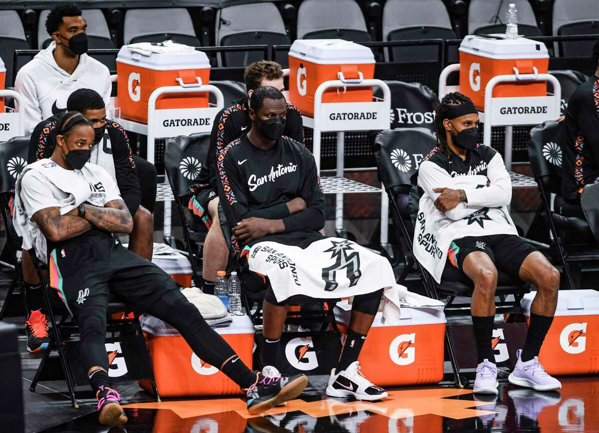 DeMar DeRozan, left, Gorgui Dieng, middle, and Patty Mills sit on the bench as time runs out on the Spurs' 125-101 loss to the Cleveland Cavaliers in the AT&T Center on Monday, April 5, 2021.