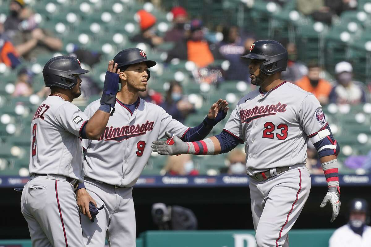 Minnesota Twins designated hitter Nelson Cruz (23) is greeted by Luis Arraez, left, and Andrelton Simmons after his grand slam during the second inning of a baseball game against the Detroit Tigers, Monday, April 5, 2021, in Detroit. (AP Photo/Carlos Osorio)