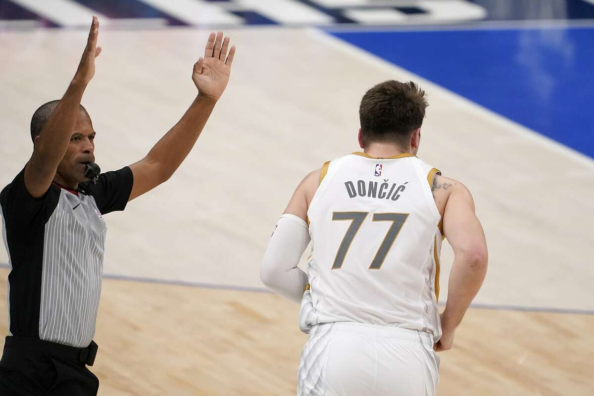 Referee Eric Lewis, left, signals as Dallas Mavericks guard Luka Doncic (77) heads down court after sinking a three-point basket in the second half of an NBA basketball game against the Utah Jazz in Dallas, Monday, April 5, 2021. (AP Photo/Tony Gutierrez)