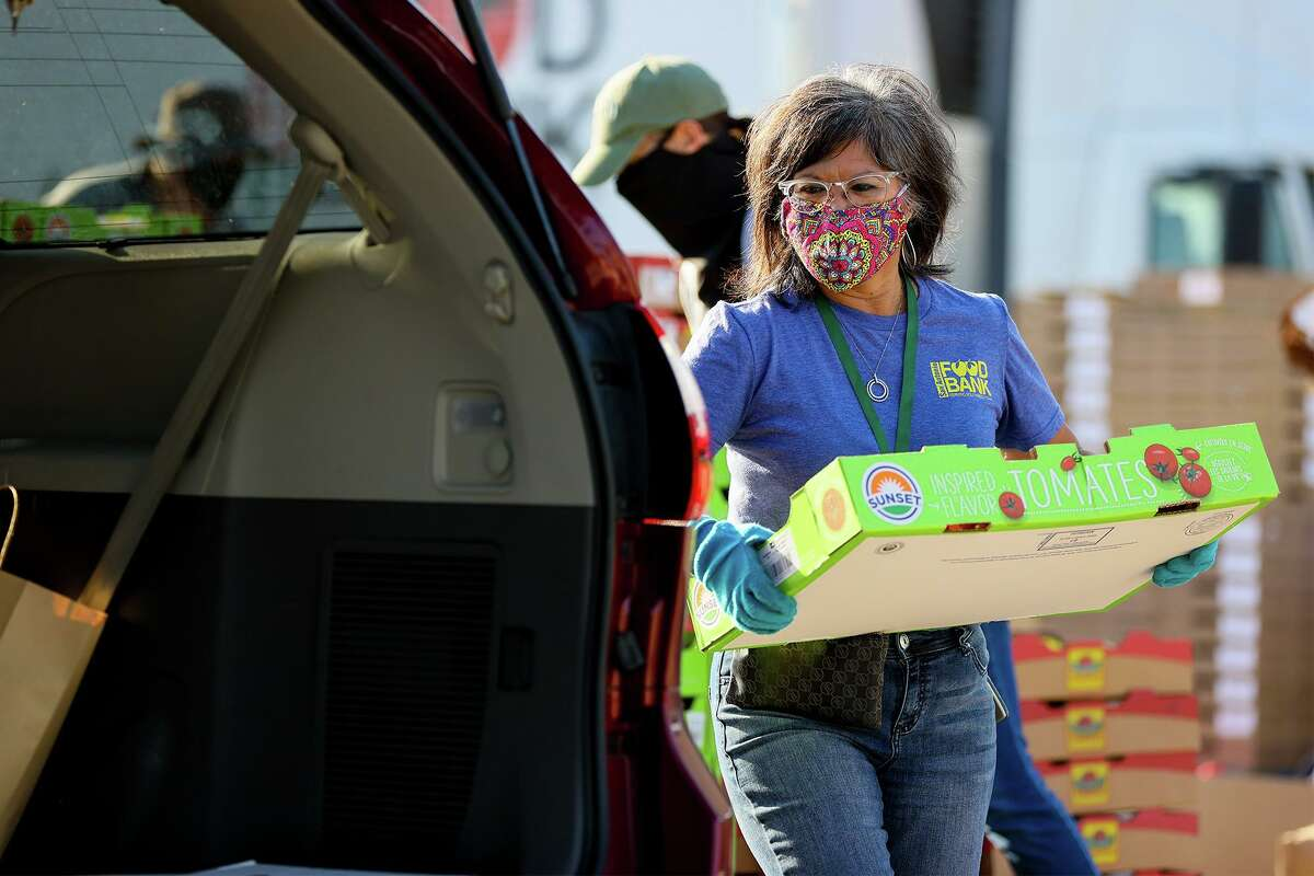 Yolanda Lopez, a volunteer with the San Antonio Food Bank, carries a flat of tomatoes to a waiting car at Toyota Field on Friday, March 26, 2021. Lopez has given over 360 hours of time since May to help those in need.