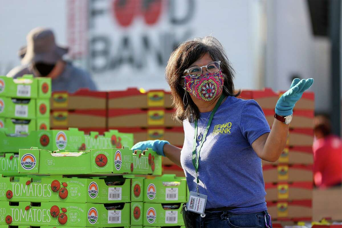 """Yolanda Lopez motions for a car to advance at a mega distribution event. """"I feel like I'm really helping,"""" she says."""