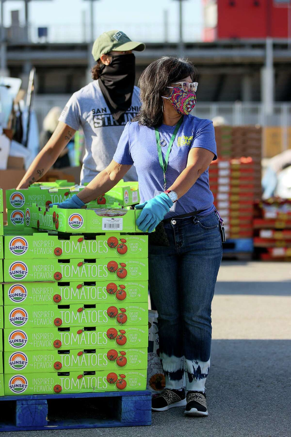 Yolanda Lopez, right, distributes flats of tomatoes with Andrea Deincentz at Toyota Field on Friday, March 26, 2021.