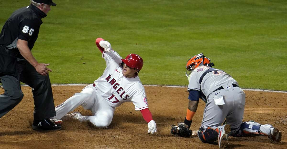 Los Angeles Angels' Shohei Ohtani (17) reacts after scoring on a fielder's choice past Houston Astros catcher Martin Maldonado on a ground ball by Jared Walsh during the eighth inning of a baseball game, Monday, April 5, 2021, in Anaheim, Calif. (AP Photo/Marcio Jose Sanchez)