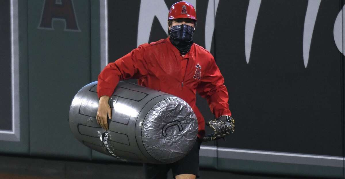 A member of the Los Angeles Angels grounds crew removes an inflated plastic trash can thrown on to the field during the sixth inning against the Houston Astros at Angel Stadium of Anaheim on April 05, 2021 in Anaheim, California. (Photo by Harry How/Getty Images)