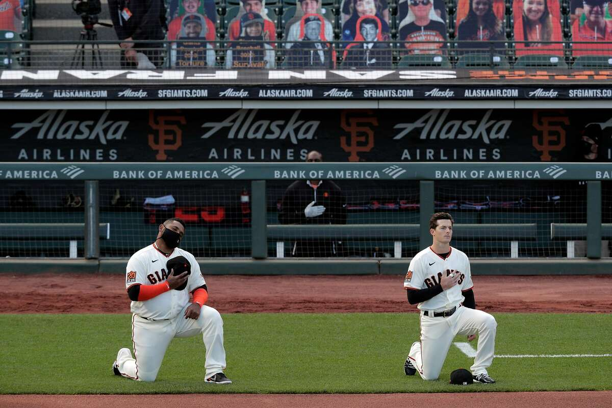 Pablo Sandoval (48) and Mike Yastrzemski (5) kneel during the national anthem before the San Francisco Giants played the San Diego Padres at Oracle Park during their home opener in San Francisco, Calif., on Tuesday, July 28, 2020.