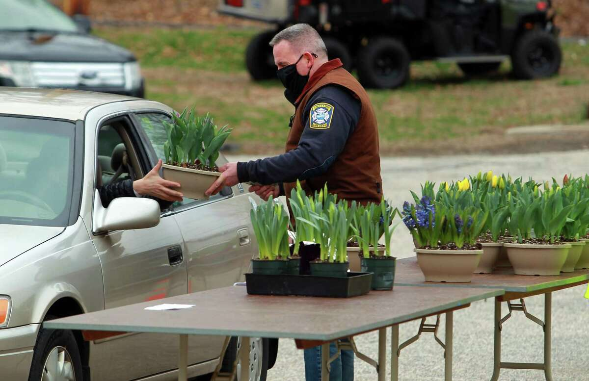 Volunteer firefighter John Recce hands a flower to a customer during White Hills Fire House's drive-thru Easter flower sale in Shelton, Conn., on Friday April 2, 2021.