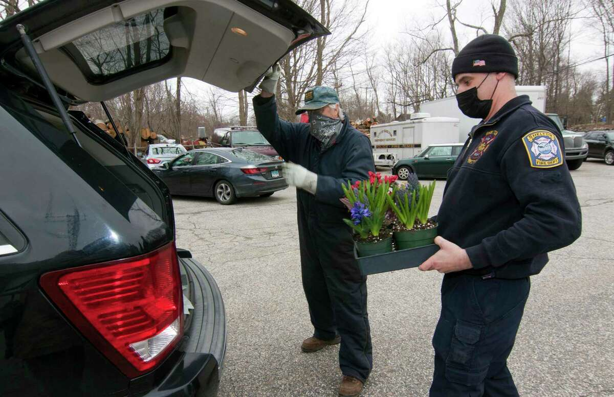 Volunteer firefighter Jim Norkus carries a flower to a customer's vehicle during White Hills Fire House's drive-thru Easter flower sale in Shelton, Conn., on Friday April 2, 2021.