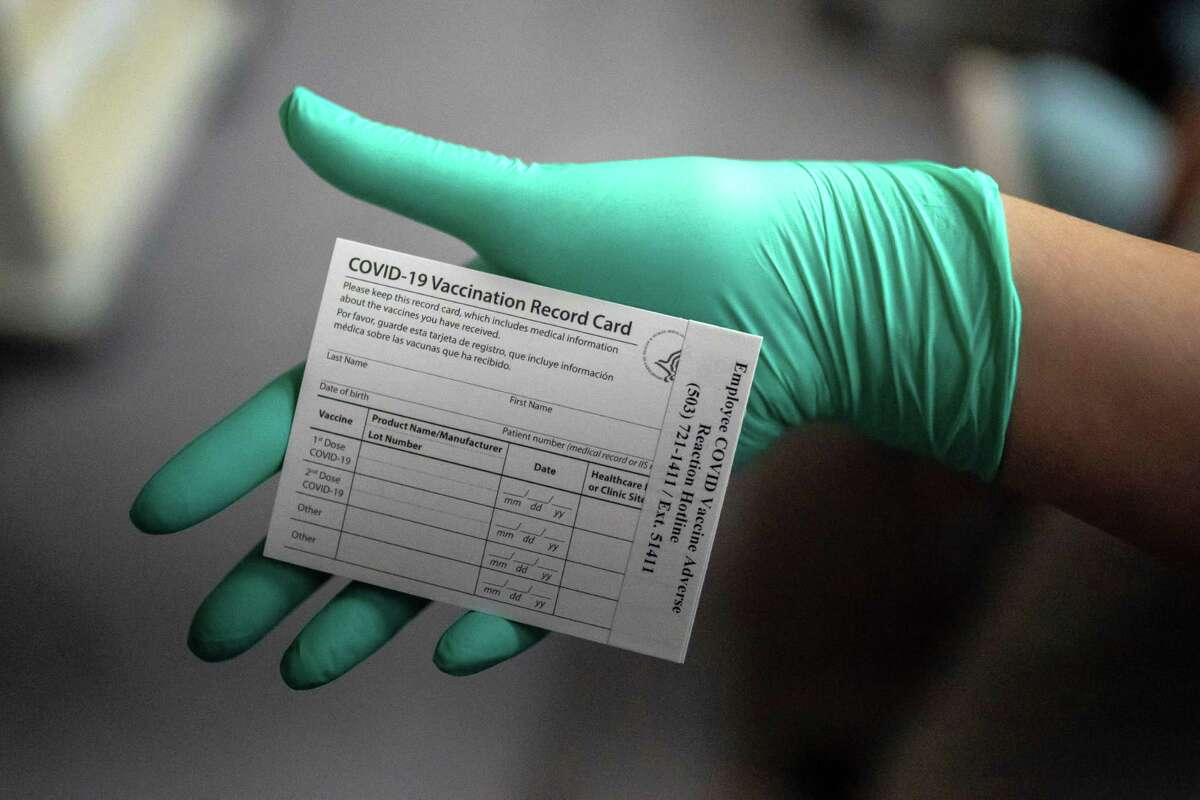 A healthcare worker displays a COVID-19 vaccine record card at the Portland Veterans Affairs Medical Center in Portland, Oregon. (Nathan Howard/Getty Images/TNS)