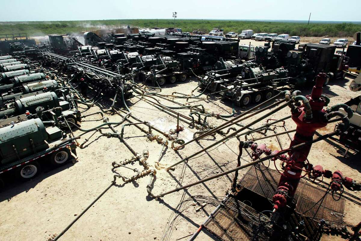 A well head, far right, is connected to pipes and hoses leading to a a partially visible fracking operation, at left and background. The operation includes manifolds and frac pumps at this Chesapeake Energy hydraulic fracturing operation near Carrizo Springs, Texas Thursday May 5, 2011. Hydraulic fracturing is a method of removing oil and gas from rock formations such as the Eagle Ford shale formation in south central Texas. John Davenport/ San Antonio Express-News