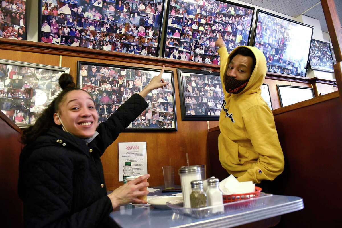Eyvonntae Washington and her husband Cory Spencer, who have been customers since they were children, point out a photo of Eyvonntae as they sit in a booth in Newest Lunch on Wednesday, March 31, 2021 in Schenectady, N.Y. The Iconic lunch spot is turning 100. (Lori Van Buren/Times Union)