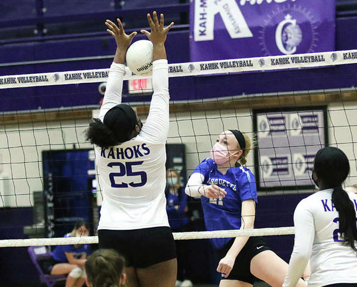 Marquette Catholic's Emma Menke (middle) hits through the block by Collinsville's Kennedy Fisher during a match earlier this season in Collinsville. On Monday night in Columbia, Menke had nine kills in the Explorers' three-set victory over the Eagles.