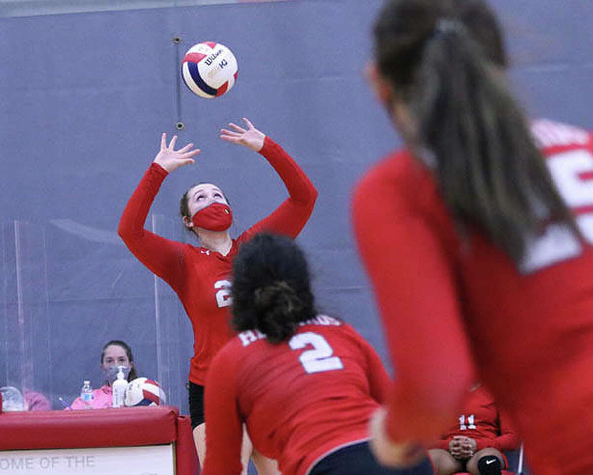 Alton setter Olivia Ducey (left) sets while two Redbird attackers Taryn Wallace (2) and Brooke Wolff go to the net in a March 27 match vs. Marquette at Alton High in Godfrey. Ducey and Wolff were honored on Senior Night before Monday's victory over Cahokia.