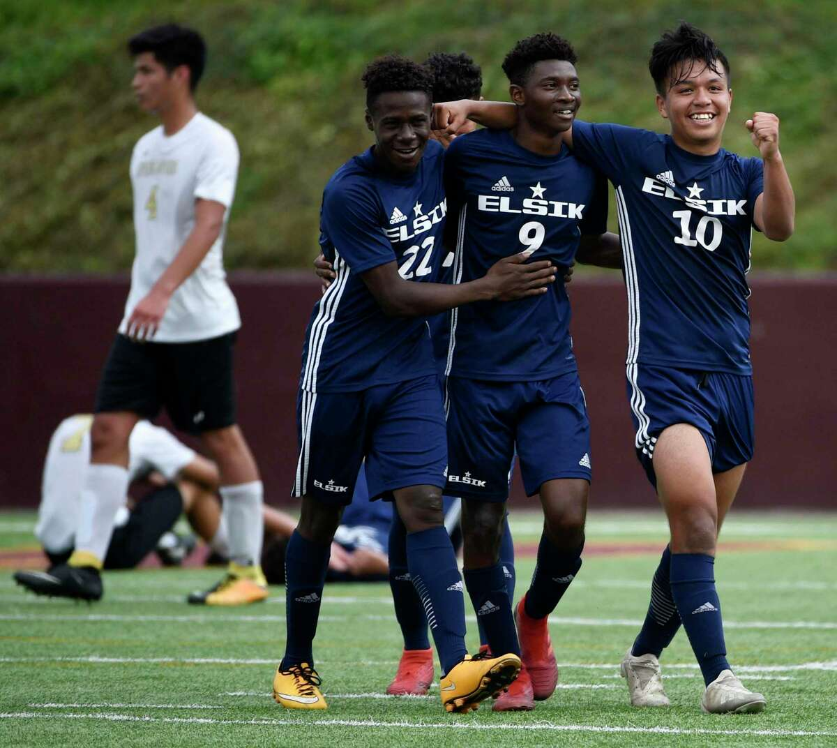 Elsik's Mayquel Aquino (22), Dandord Ndabah (9), and Edgar Rentaria celebrate the team's win over Spring Woods in a 6A region 3 final high school soccer match, Saturday, April 13, 2019, in Deer Park.
