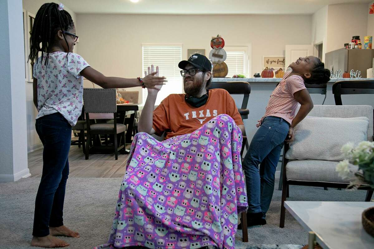 John Vargas Jr. spends time with his daughters, Leilani, 9, left, and Mariah, 8, after surprising them when he arrived in San Antonio from Florida on October 23, 2020.