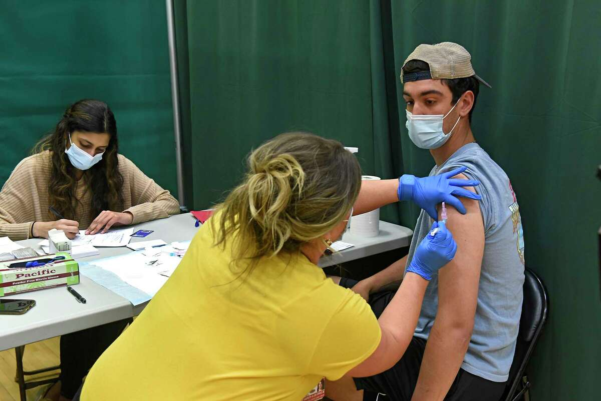 Registered nurse Kristen Hallett administers junior Arlo Marynczak's first Pfizer COVID-19 vaccine at Siena College on Tuesday, April 6, 2021 in Loudonville, N.Y. Pre-med Siena student and volunteer Azka Hasan, left, takes care of the paperwork. 500 Siena students pre-registered for the clinic. (Lori Van Buren/Times Union)