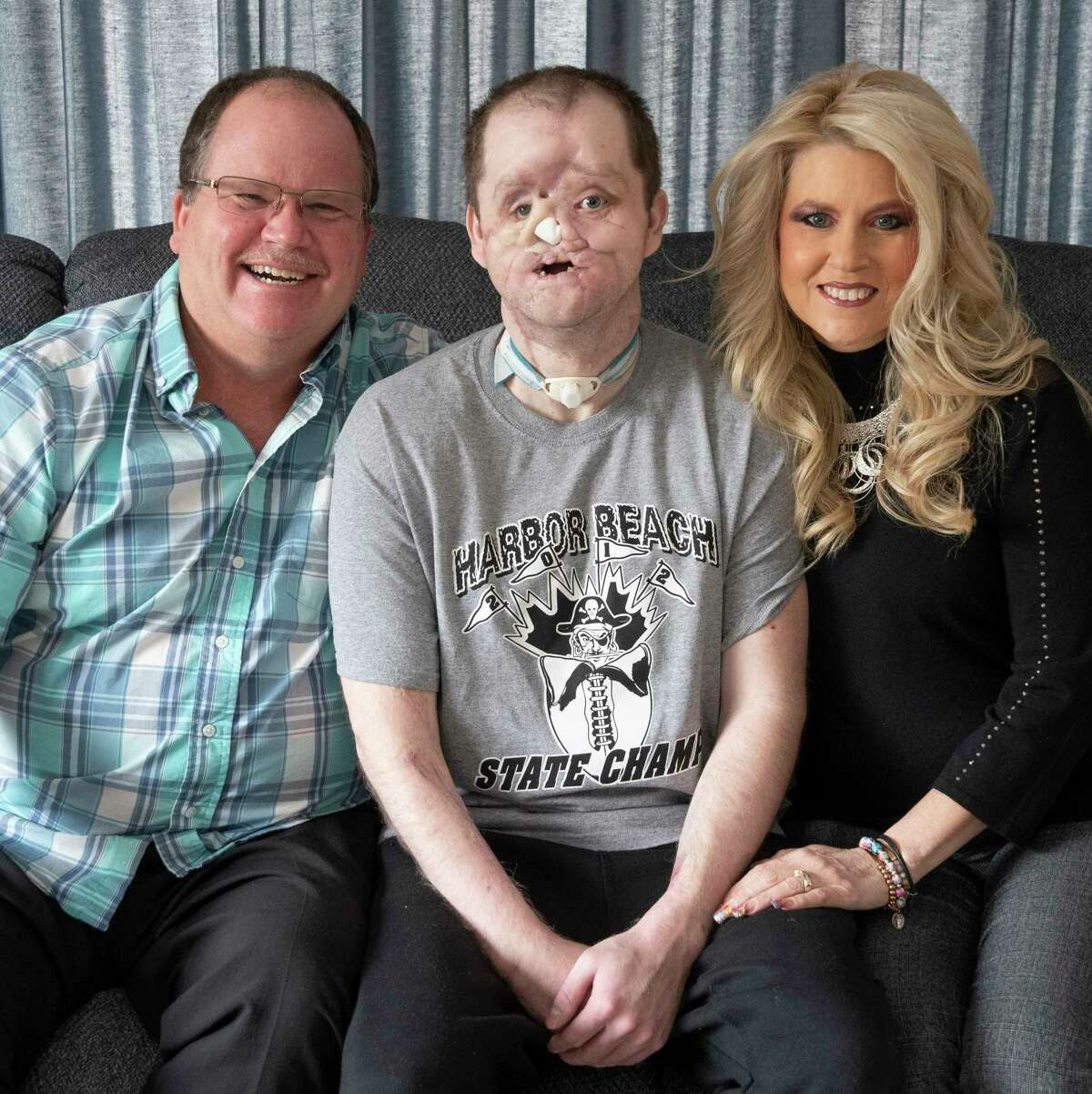 Jerry, Derek and Lisa Pfaff pose for a photo in their Harbor Beach home. The Pfaff family is working to raise $1 million to fund the cost of a face transplant operation for Derek, who was injured in 2014 he attempted to take his own life. (Pfaff Family/Courtesy Photo)