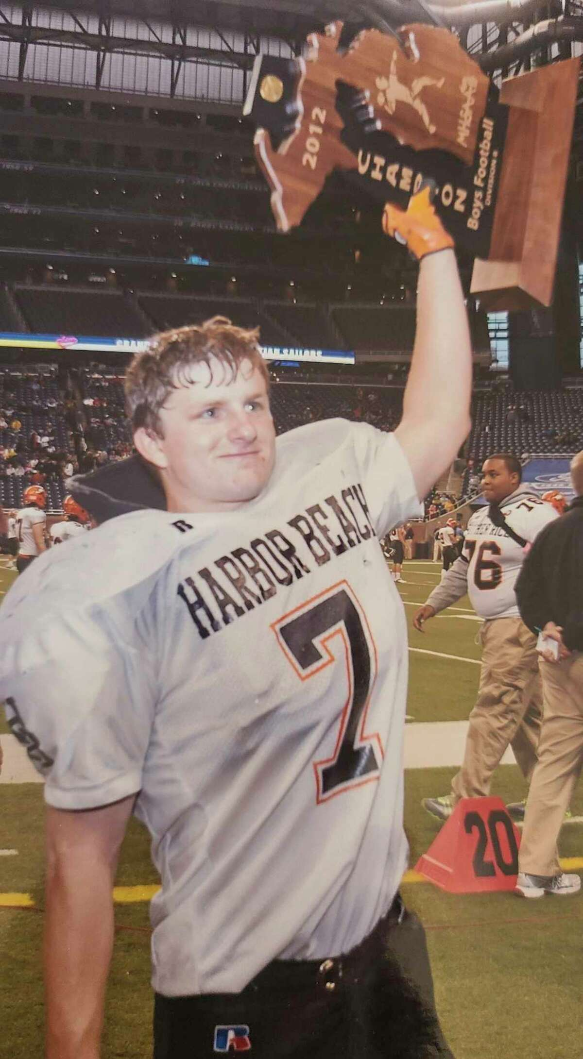 Derek Pfaff raises Harbor Beach's 2012 state football championship trophy at Ford Field. Derek was an all-state running back for the Pirates. The Pfaff family is working to raise $1 million to fund the cost of a face transplant operation for Derek, who was injured in 2014 he attempted to take his own life. (Pfaff Family/Courtesy Photo)