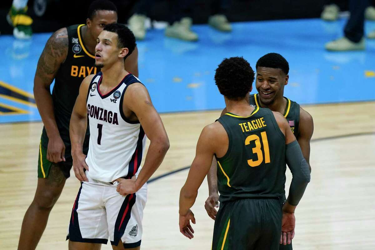 Baylor guard Jared Butler, right, celebrates with teammate guard MaCio Teague (31) in front of Gonzaga guard Jalen Suggs (1) at the end of the championship game in the men's Final Four NCAA college basketball tournament, Monday, April 5, 2021, at Lucas Oil Stadium in Indianapolis. (AP Photo/Michael Conroy)