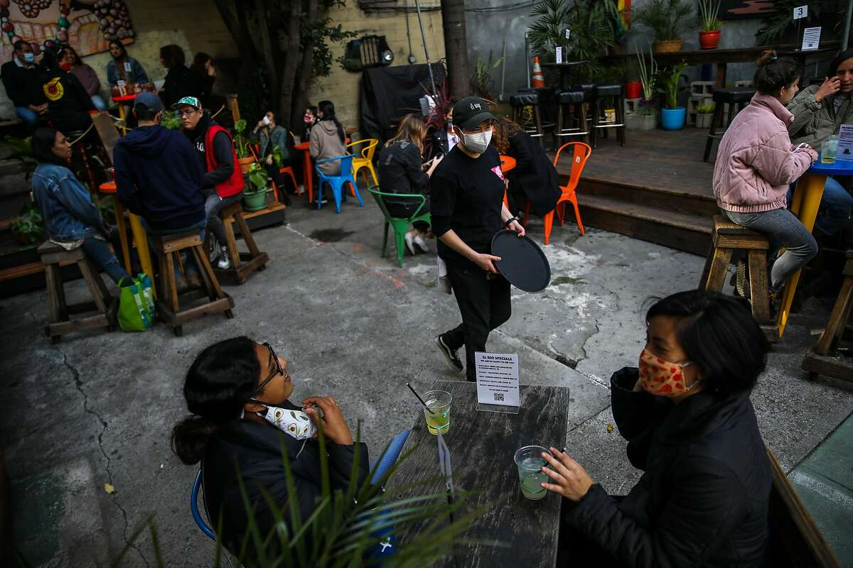 Shivani Rangwala, bottom left (donning avocado mask), and her friend Elin Chee, bottom right (donning fig mask), listen to manager Cynthia Martinez as she converses with them during their visit to El Rio, located at 3158 Mission St., on Saturday, April 3, 2021, in San Francisco, Calif. California will retire its color-coded pandemic blueprint on June 15 and allow almost all sectors of the economy, in all 58 counties, to reopen at or near full capacity, state officials said Tuesday.