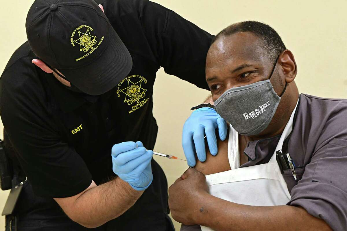James Mudge of the Albany Sheriff's Department administers a COVID-19 vaccine into the arm of Capital City Rescue Mission chef Wesley Pollack at a pod set up at the Capital City Rescue Mission on Tuesday, April 6, 2021 in Albany, N.Y. (Lori Van Buren/Times Union)