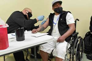 Brian Wood of the Albany Sheriff's Department administers a COVID-19 vaccine into the arm of Nelson Martinez at a pod set up at the Capital City Rescue Mission on Tuesday, April 6, 2021 in Albany, N.Y. (Lori Van Buren/Times Union)
