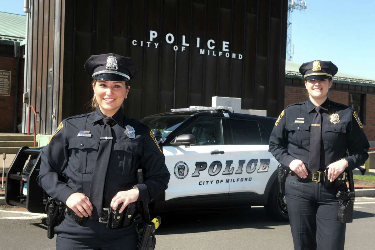 Milford Police Officers Nikki McMahon, left, and Kathleen Bruno pose in front of police headquarters, in Milford, Conn. April 5, 2021.