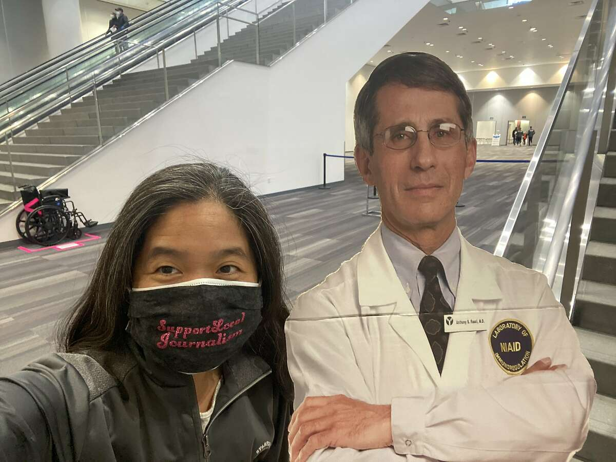 Chronicle columnist and author Vanessa Hua poses for a photo with a cutout of Dr. Anthony Fauci after receiving her second dose of the Pfizer COVID-19 vaccine at the Moscone Center in San Francisco on March 19.
