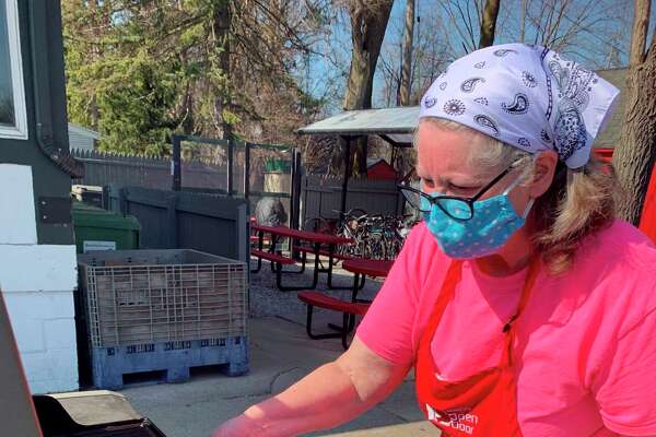 Volunteer Donna List is pictured grilling pork loin outside for the Open Door Easter dinner. (Photo Provided)
