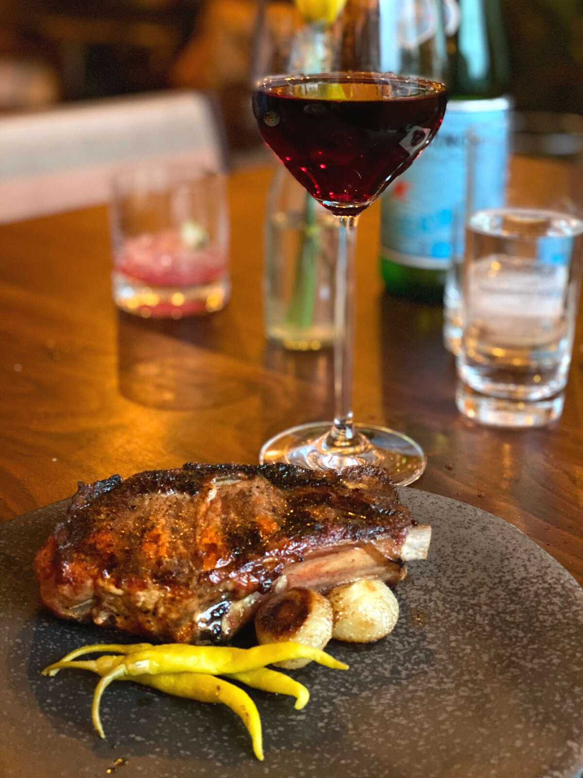 Roasted cipollini onions and pickled peppers accompany a $27 wood-grilled pork chop at Feast & Floret in Hudson. (Susie Davidson Powell/For the Times Union.)