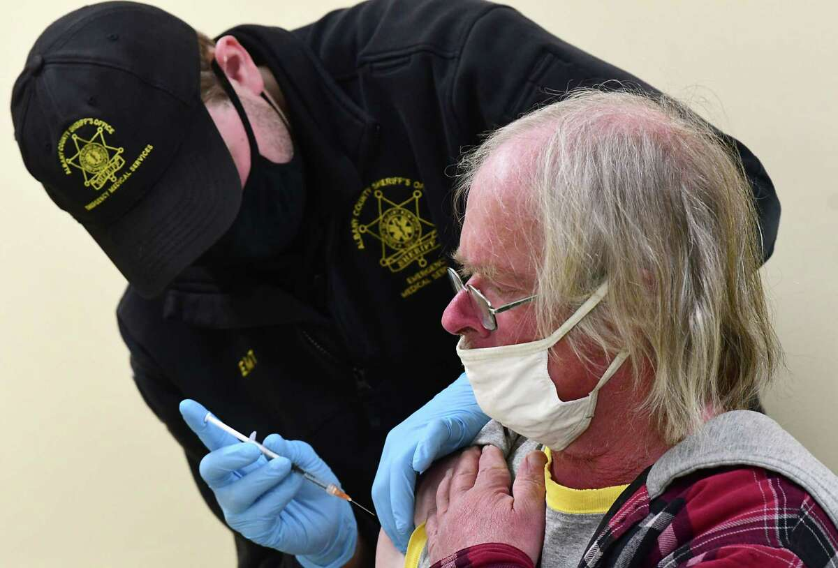 James Mudge of the Albany Sheriff's Department administers a COVID-19 vaccine into the arm of a man at a pod set up at the Capital City Rescue Mission on Tuesday, April 6, 2021 in Albany, N.Y. (Lori Van Buren/Times Union)