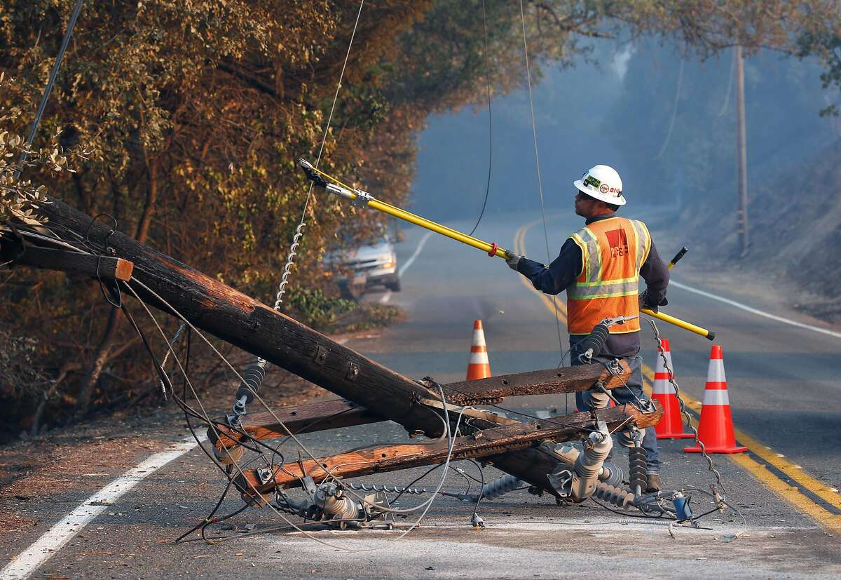 A PG&E worker severs the power line from a fallen utility pole on Geysers Road as the Kincade Fire burns near Geyserville in October 2019.